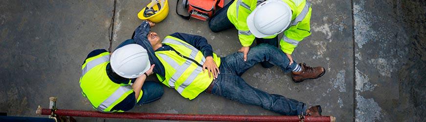 Scène d'accident sur un chantier. Deux personnes portent secours à un homme allongé à terre. Les trois individus portent un gilet jaune à bandes réfléchissantes