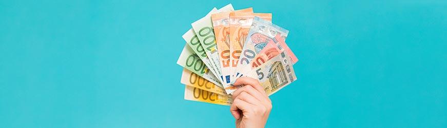 Photo d'une main, sur fond bleu, tenant des billets de banque, de 5, 10, 50, 100 et 500 euros, en éventail à la façon d'un jeu de carte.