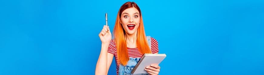 Jeune fille souriante sur fond bleu. Elle lève son stylo en l'air comme si elle avait une idée. Dans l'autre main, elle tient un bloc-notes