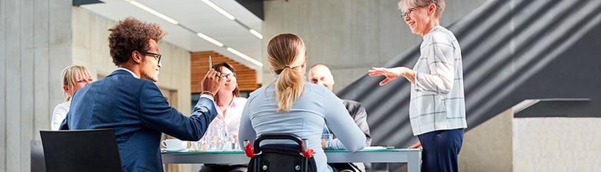 Six personnes dans un bureau, autour d'une table pendant une réunion. Une des personnes prenant part à la discussion est sur un fauteuil roulant, de dos