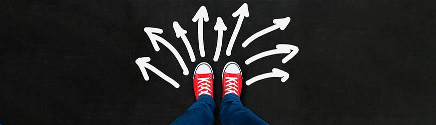 Photo de pieds chaussés de baskets rouges. Devant, sur le sol noir, des flèches blanches indiquent des directions à 180°