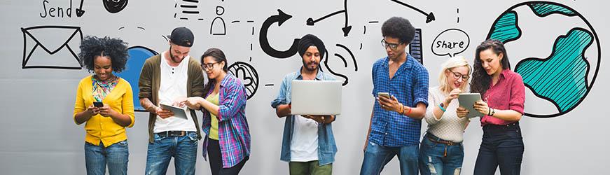 Au premier plan, sept personnes, d'environ 25 ans, quatre femmes et trois hommes se tiennent debout devant un mur illustré par un schéma géant composé de différentes icônes (terre, enveloppe, flèches). Ils ont tous à la main un ordinateur, un smartphone ou une tablette et semblent interagir ensemble.
