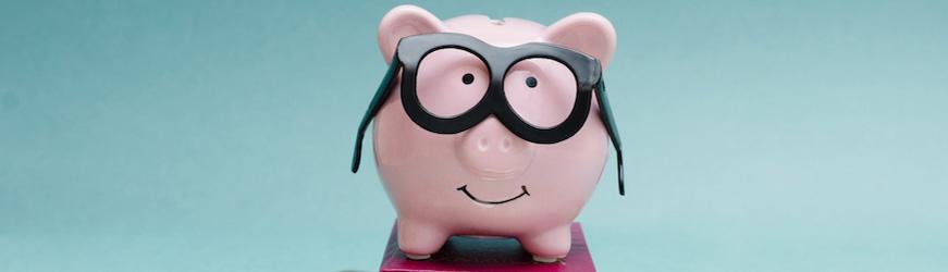 tirelire cochon rose portant des lunettes, posée sur un livre.