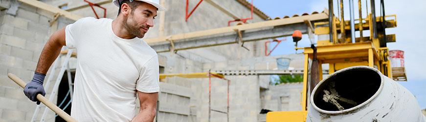 Ouvrier charriant du sable dans une bétonneuse sur un chantier de construction.
