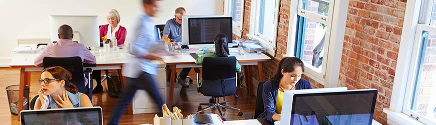 Scène d'activité dans un bureau. Des personnes sont assises devant leur ordinateur. Une personne traverse rapidement l'open space. Le tout dans une ambiance dynamique
