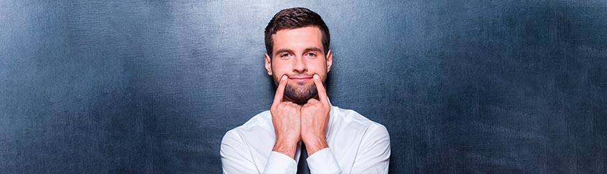 Jeune homme brun en chemise blanche, se tirant les lèvres de chaque côté du visage pour se faire sourire