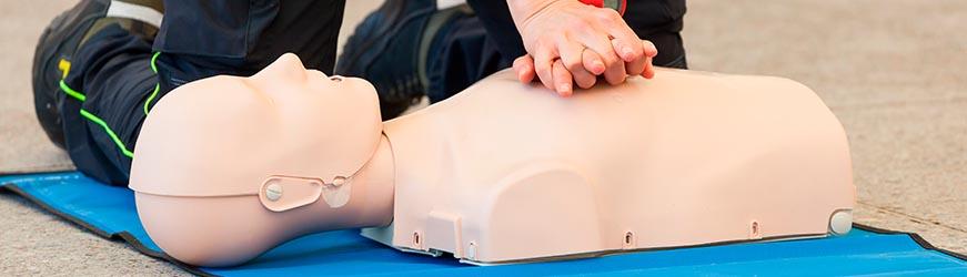 Mains d'un secouriste prodiguant un massage cardiaque à un mannequin.