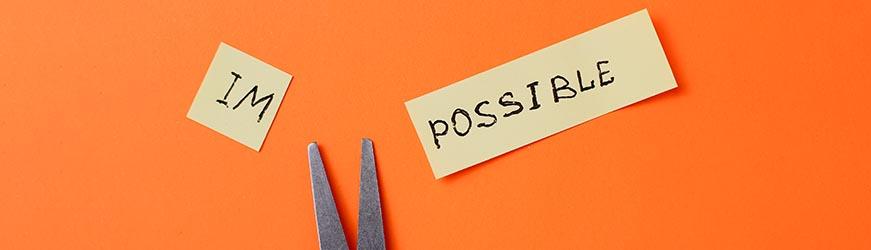 Étiquette avec le mot impossible coupée en deux et formant les mots im et plus loin possible. Les lames de la paire de ciseaux apparaissent au milieu