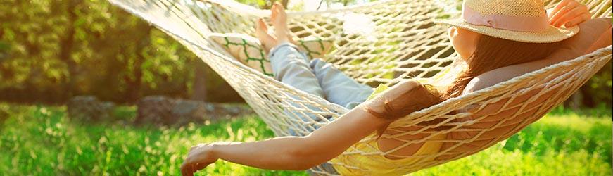 Femme, portant un chapeau de paille, allongée dans un hamac. La scène se situe dans un cadre de verdure.