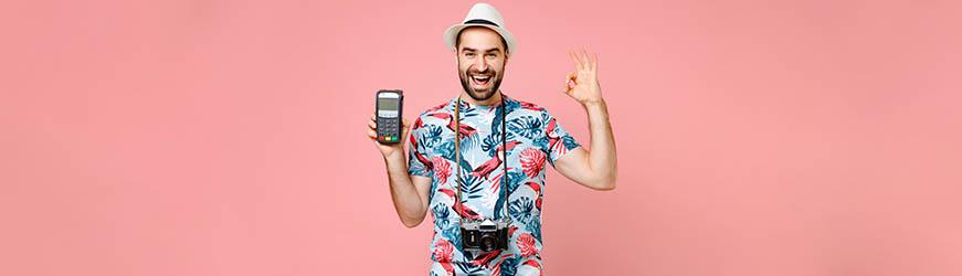 Jeune homme de face sur fond rose. Il porte un chapeau de paille, une chemise à motifs exotiques et en appareil photo en bandoulière. Il brandit d'une main un terminal de paiement en souriant et, de l'autre, il fait le signe OK.