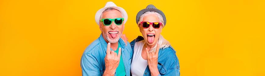 Un homme et une femme d'âge mûr sur un fond jaune vif. Ils portent des chapeaux et de lunette de soleil colorés. Ils tirent la langue de façon provocatrice en souriant et font un signe rock n roll de la main.