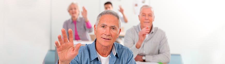 Hommes et femmes d'âge mûr, assis les uns derrière les autres, comme dans une salle de classe. Ils lèvent la main pour poser une question.